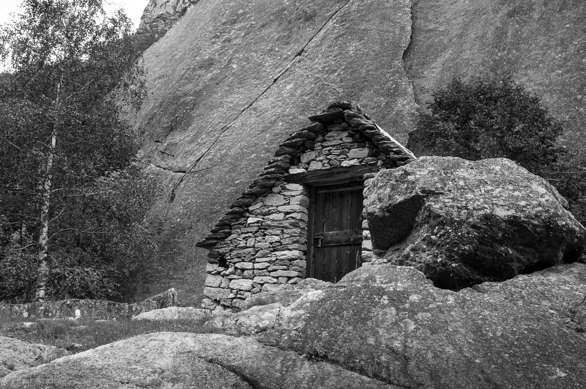 Hütte im Val Calnegia unter einem Felsen
